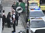 Officers and paramedics treat a 14-year-old boy who was stabbed in Islington tonight