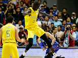 Thon Maker (centre) of Australia attempts to kick Terrence Romeo (right) of the Philippines