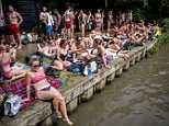 People sunbathe in Hampstead Heath Mixed Bathing Pond in north London on Sunday, July 1