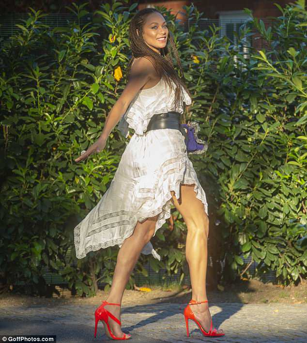 Strutting her stuff:The model, 42, looked in a jubilant mood as she paraded her long pins in a billowing ruffle-hem dress while confidently sauntering through the sun-drenched streets