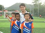 Ekapol Chanthawong, pictured with young football players he coached, was the only surviving member of his family when they were struck down with a killer disease at their home in Northern Thailand in 2003