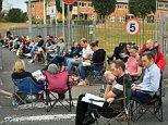 Parents queue in line outside Ysgol Y Berllan Deg school, Cardiff, for the breakfast club registration today