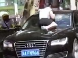 Shocking video footage shot by witnesses in Nanjing city shows the woman sitting on the bonnet of a black Audi saloon, reportedly with her husband and his mistress in it
