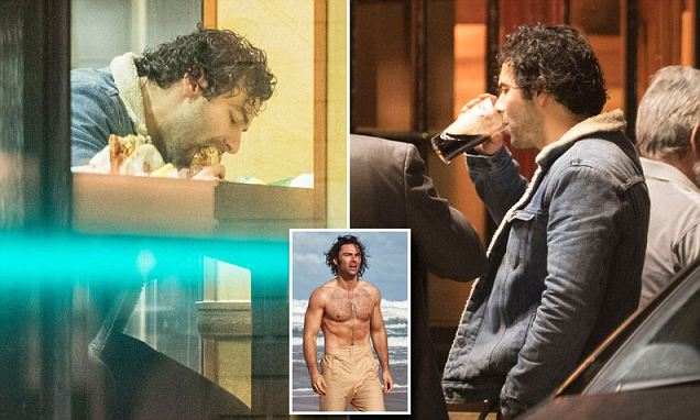 Aidan Turner downs a pint of Guinness and tucks into a sub roll on night out