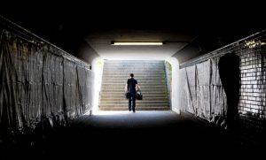 Ein Mann geht aus einem dunlen Tunnel heraus. Draußen ist Tag.