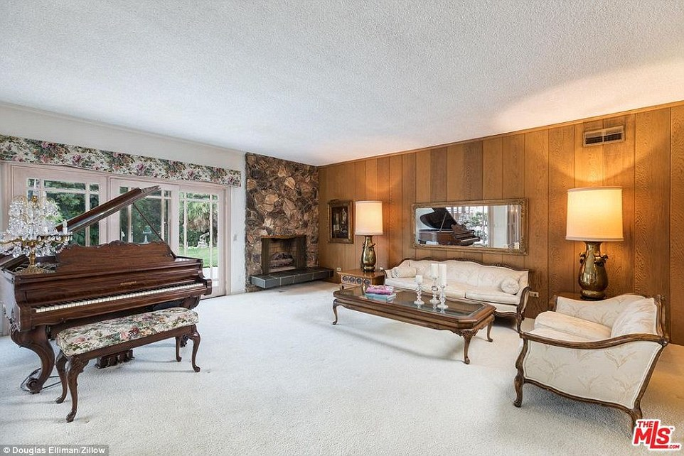 Old school: Vintage elements of the home include a rock-wall fireplace, bold wood paneling and an abundance of floral prints