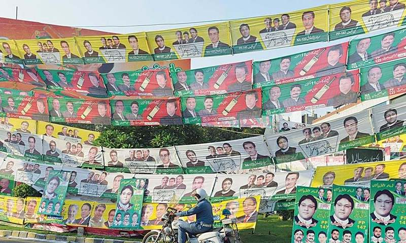 A policeman on his motorbike passes by a road decked with PTI and PMLN banners for the NA-122 by election in Lahore on Sunday | Photo by Arif Ali, White Star