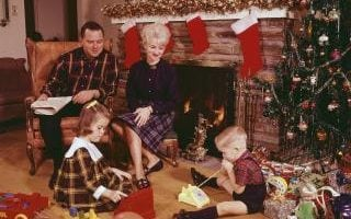A man and woman sit by a fireplace hung with stockings, as a young boy and girl play with their new presents