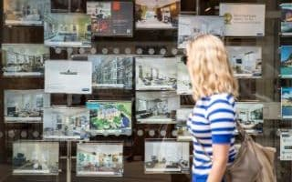 A woman walks past an estate agent's window display