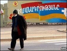 Man walks past mural of flag of breakaway Nagorno Karabakh region
