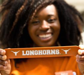 Image of a happy Long Horn student holding a Longhorn banner.