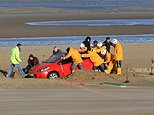 Photographs of a red Mazda  on Rhyl beach in Wales swamped by the over night tide began to emerge on social media