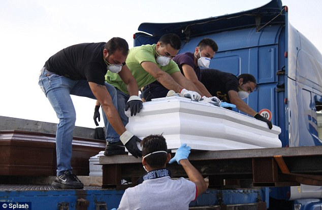A small coffin belonging to the victim of the October 3 tragedy in which more than 300 people drowned is unloaded at port in Sicily after arriving from Lampedusa