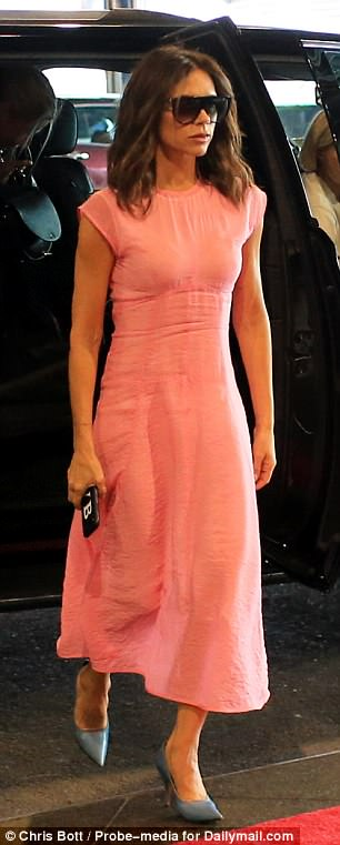 Style icon: Victoria looked chic in a mid-length pink silk dress with blue heels and oversize shades