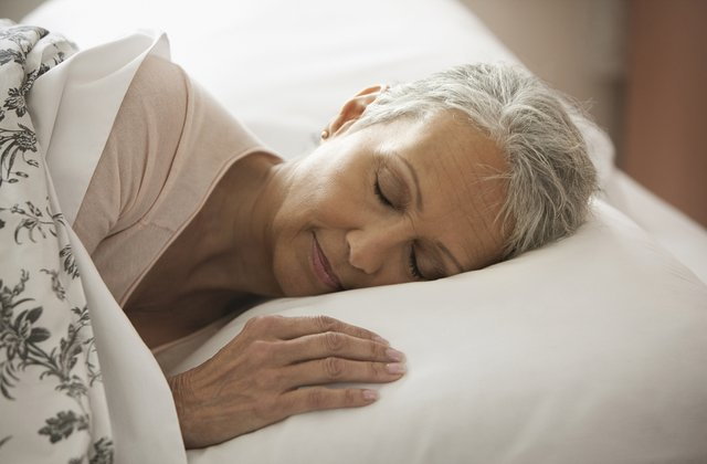 Older woman sleeping in a bed.