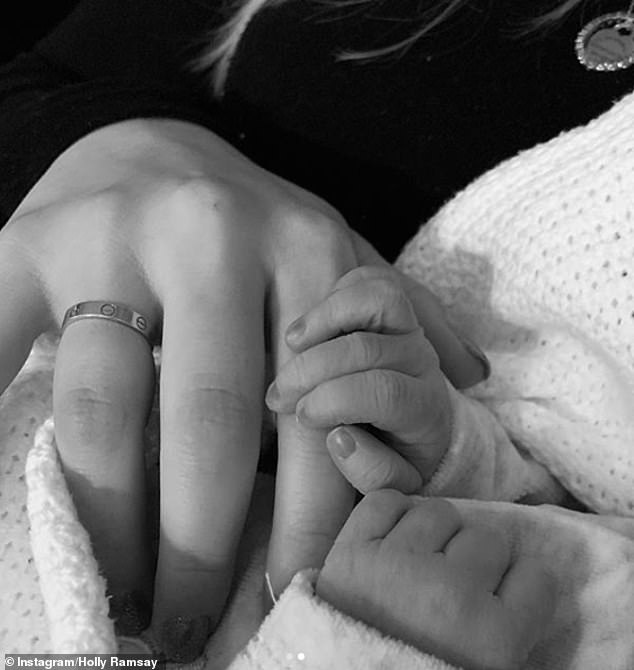 Sibling bond:Holly also shared a beautiful photo cradling Oscar, with another black and white snap of her holding Oscar's tiny hand
