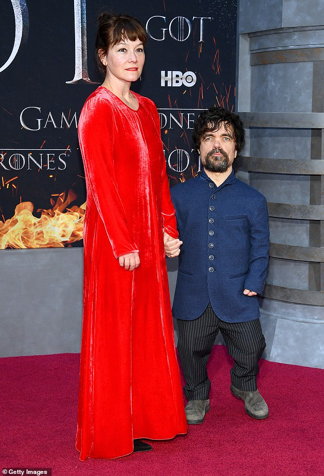 Peter and Erica:Dinklage was wearing black pants with white pinstripes with a long-sleeved blue buttoned shirt along with work boots
