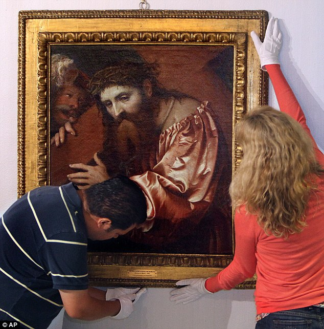 In this Nov. 4, 2011 photo, Jose Luis Aguirre (left) and Michelle Smith Grindberg carefully remove 'Christ Carrying the Cross Dragged by a Rogue' from the Brogan Museum and ready it for transport, inTallahassee