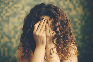 A person with curly hair covering their face with their hands.