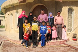 The Ismams, a Mandaean displaced family, pose at the entrance of the Mandaean Council in Kikruk. Credit: Karlos Zurutuza/IPS