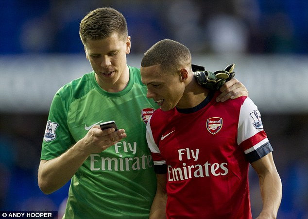 Handywork: Szczesny and Gibbs assess the goalkeeper's photography skills as they head off the pitch