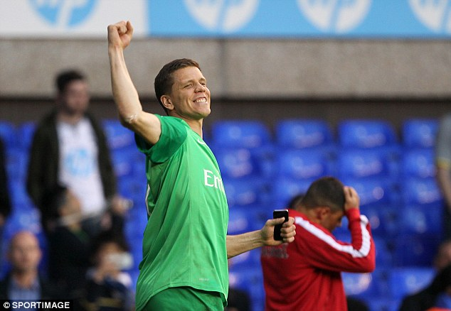 Delighted: Szczesny turns in the direction of happy Arsenal supporters and punches the air