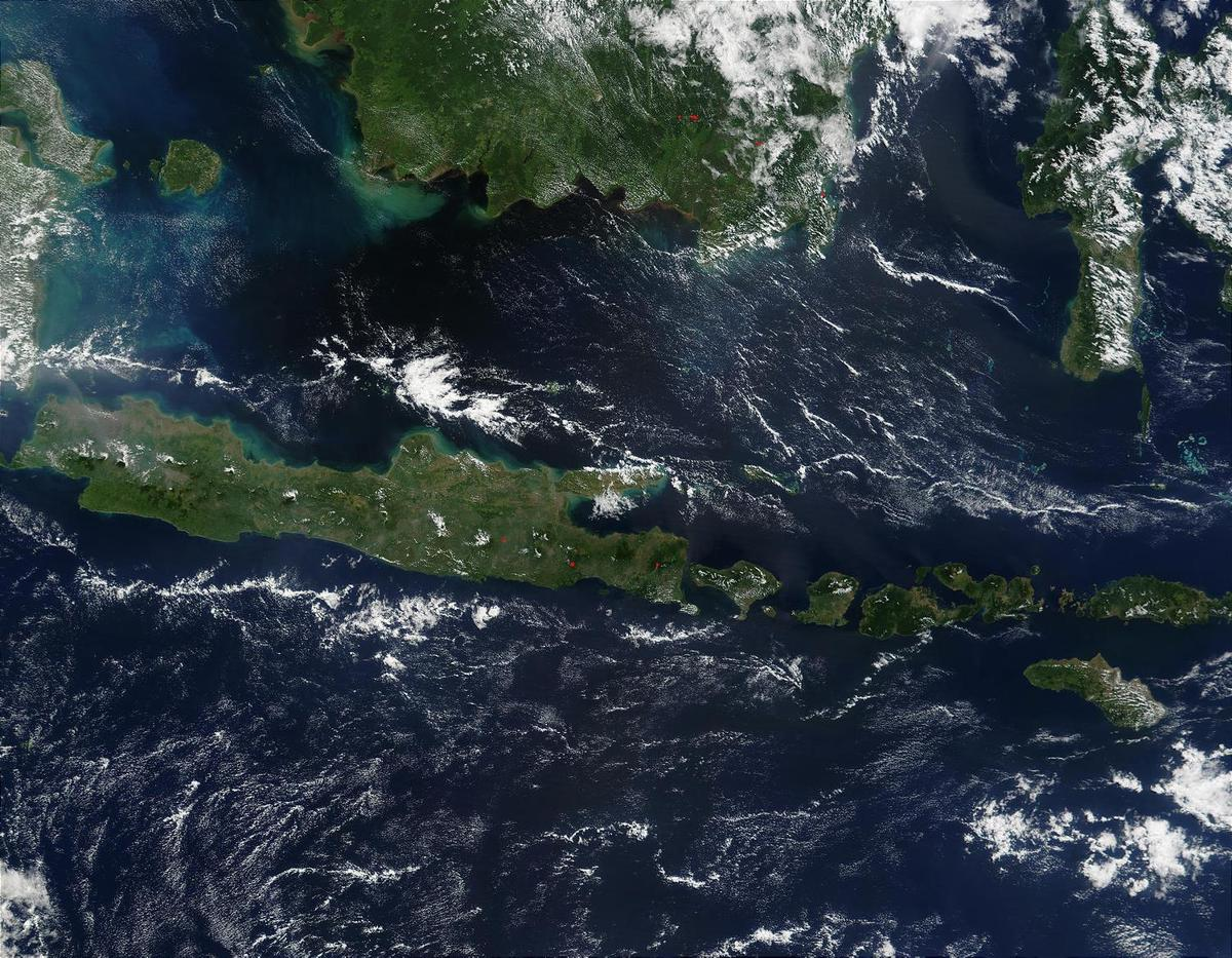 This true-color image of some of the Indonesian islands is from mid-May 2002. Fire season was not fully underway in the region, and skies over the large island of Borneo (top) were partially cloud-covered, but not hazy with air pollution. The horizontally situated island of Java appears to be experiencing some haze at its western end, and a few scattered fires (red dots) are apparent. Image courtesy of NASA.