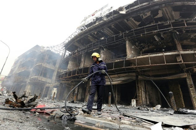An Iraqi firefighter works at the site of a Baghdad bombing claimed by the Islamic State group on July 3