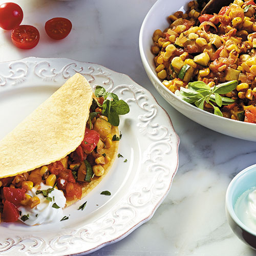 corn and zucchini tacos on plate and bowl