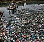 "FILE - In this Sunday, Oct. 2, 2016 file photo, a man guides a raft through a polluted canal littered with plastic bags and other garbage in Mumbai, India. United Nations officials say nearly all of the world's countries have agreed on a deal to better manage plastic waste, with the United States a notable exception. A ""legally binding framework"" that affects thousands of types of plastic waste emerged Friday, May 10, 2019 after a two-week meeting of U.N.-backed conventions on plastic waste and toxic chemicals. (AP Photo/Rafiq Maqbool, file)"