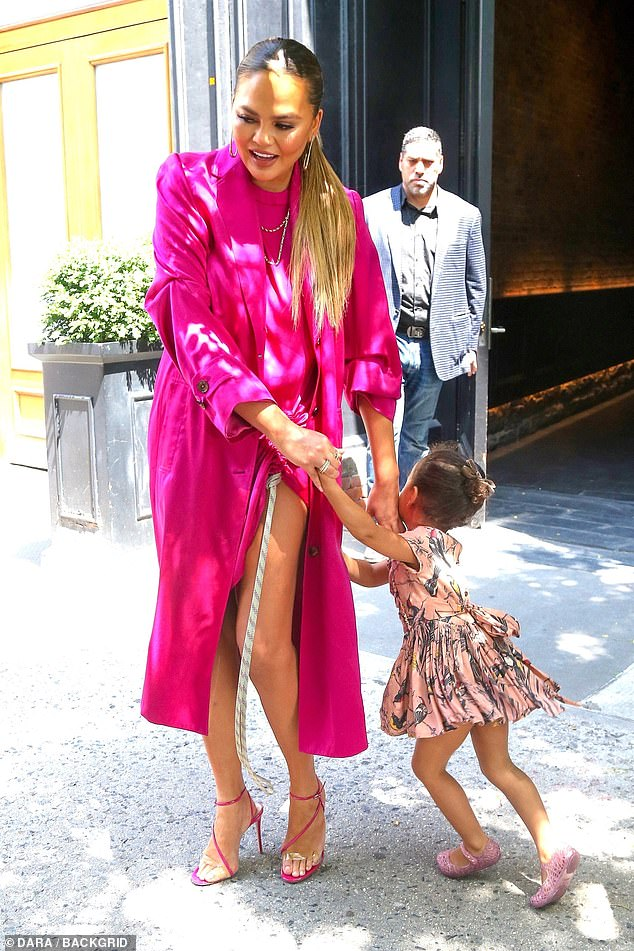 Mothering skills: The model, who wowed in a high-neck bright pink dress which showcased her long legs with its daring split, smiled as her daughter put on a sprightly display