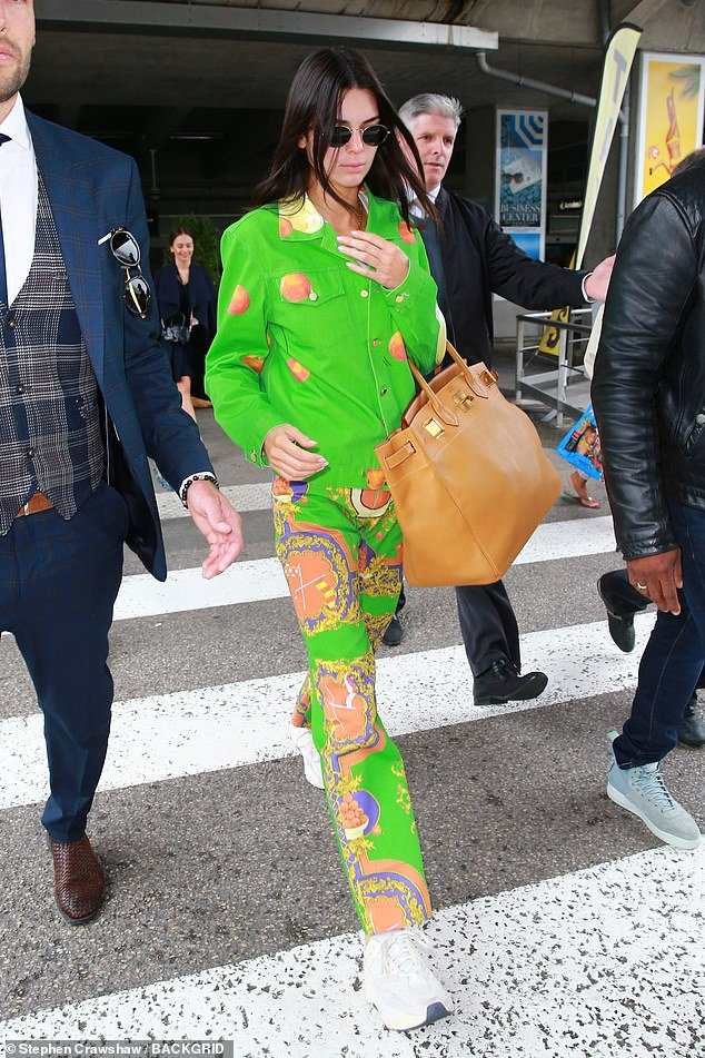 Strutting her stuff:The 23-year-old Keeping Up With The Kardashians star joins a legion of supermodels in making appearances at the annual affair and she was sure to make a statement while landing as she donned a bold neon ensemble with a Hermès Birkin bag