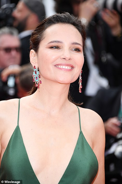 Glamorous in green: Virginie completed her look with a pair of statement drop earrings