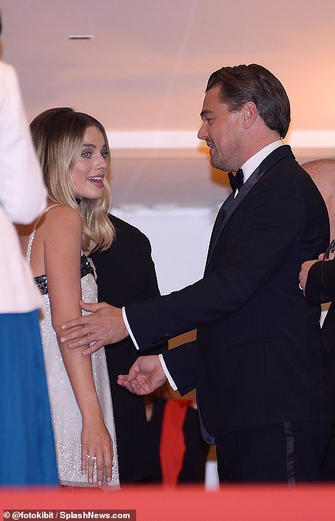 Pals: Margot and Leo put on a friendly display behind the scenes at the star-studded screening