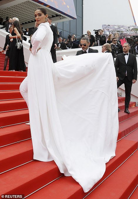 Helping hand: The star's train needed to be carried up the stairs by a member of her entourage