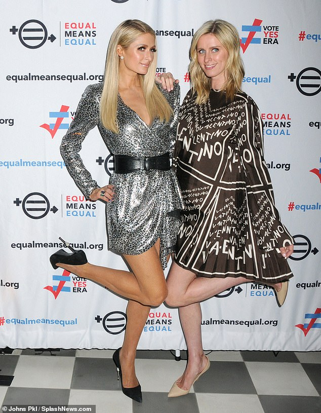 Girl talk: Paris Hilton wowed in a silver mini as she joined sister Nicky in a Valentino cape at Equal Means Equal campaign launch at the Times Square Edition Hotel in New York on Tuesday