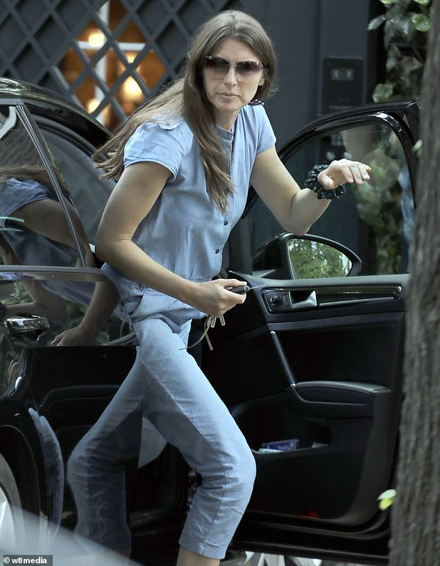 Stepping out of her car in a denim play suit she kept her sunglasses on and had her long brunette locks worn down