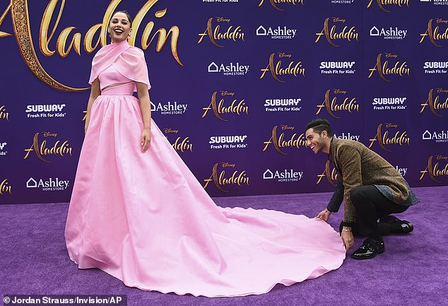 Assistance:While on the purple carpet outside Disney's El Capital Theatre, Mena, 27, sank to a crouch and helped Naomi, 26, adjust the train of her gown