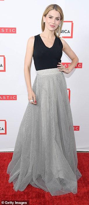Hilaria, 35, wore an ensemble of sleeveless black top with full-length metallic knit skirt