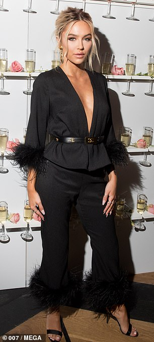 Glam: Delilah looked effortlessly chic as she went braless for the event in a black feathered plunging blazer with matching cropped trousers