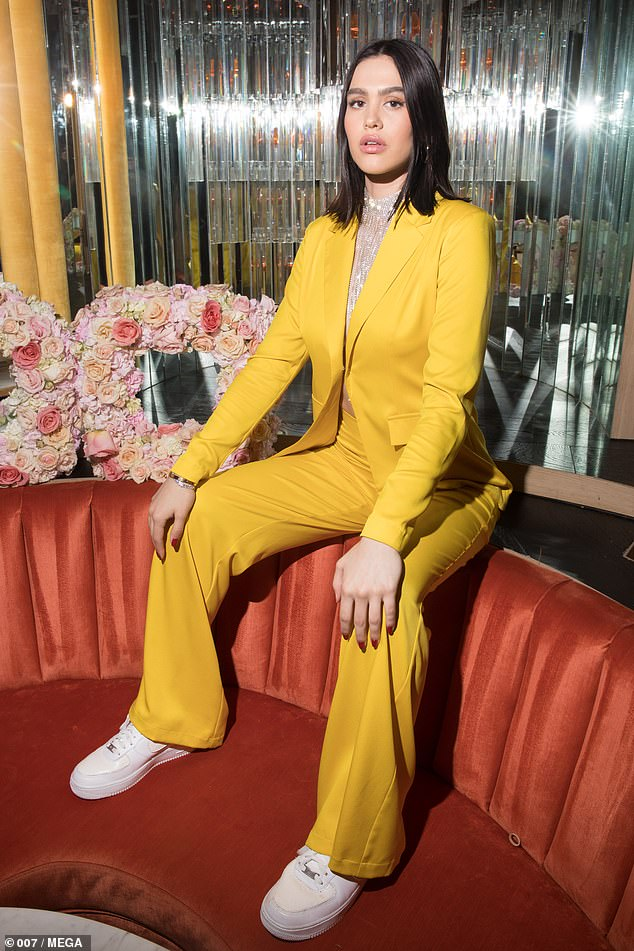 Stylish: She finished her look with white platform trainers and she styled her brunette locks into a blow-dried hairdo, she added a slick of glamorous make-up