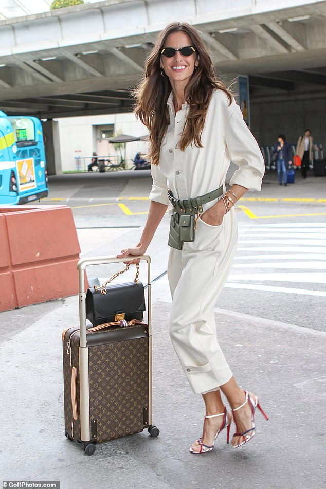 Standing tall: Upping the style ante, the supermodel boosted her frame in a pair of trendy red strappy heels