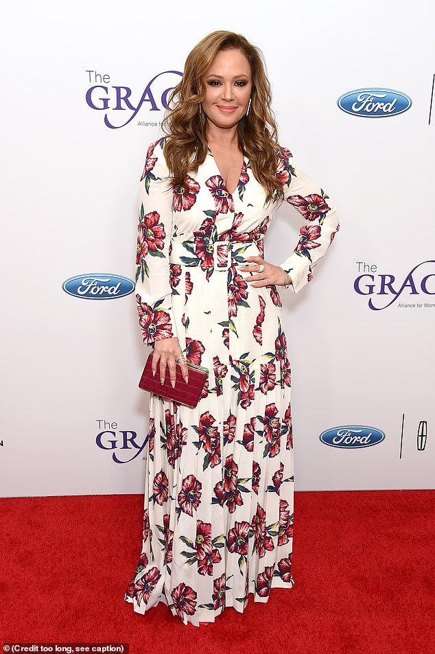Hand at the waist: The King Of Queens star modeled an elegant blue, yellow, red and white floral gown, accessorizing with a scarlet clutch