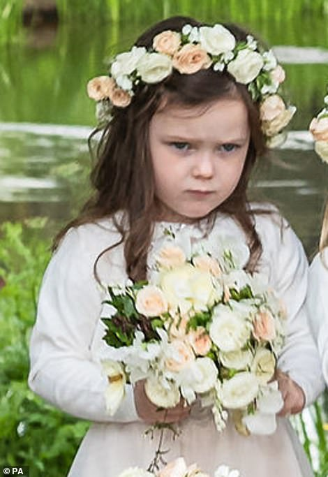 All eyes are drawn to little Aurelia, who scowls away from the camera while clutching her bouquet firmly in both hands