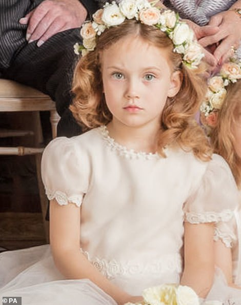 In both photos the five-year-old sits side-by-side with her lookalike little sister, Isabella