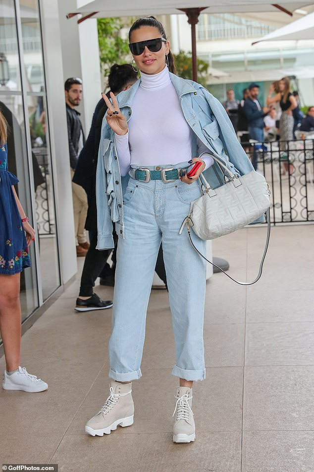 So chic: With her light blue denim jacket draped over her shoulders, Adriana kept the chill at bay in a demure turtleneck long-sleeved top