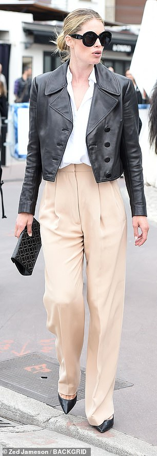 Model arrival: Doutzen later stepped out in a white blouse and beige trousers