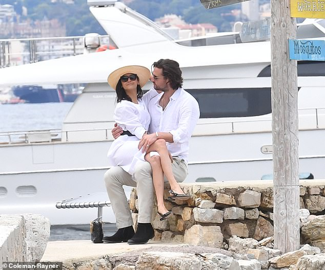 PDA: Dobrev, 30, who wore a wide-brimmed straw hat and shades, snuggled up to her beau as she perched on his lap while he sat on a seaside wall in the French resort