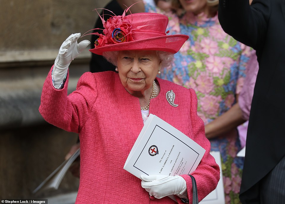 The Queen offers the crowds a wave as she stands with other members of the royal family outside St George's Chapel