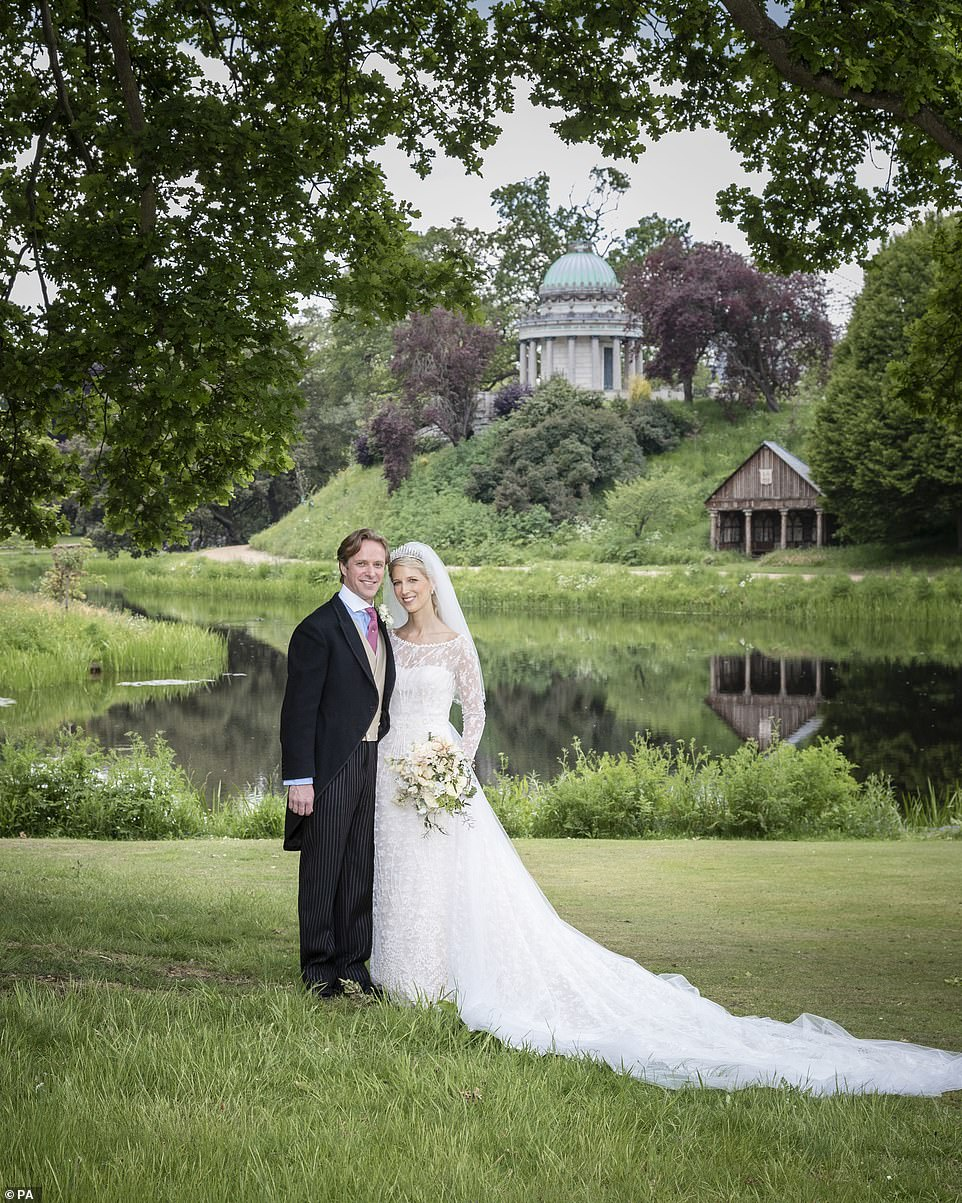 Another stunning image was taken by photographer Hugo Burnand after the wedding at St George's Chapel and shows Lady Gabriella and Mr Thomas Kingston in front of the lake at Frogmore House, with her magnificent train spread out behind her
